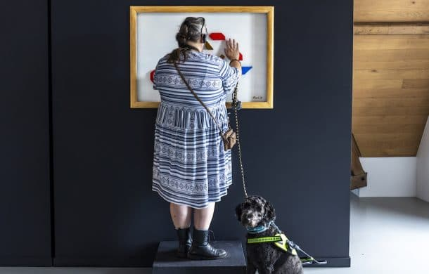 A blind visitor touches artwork at The Blind Spot exhibition